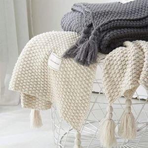 deux plaids à pompon en laine sur un canapé